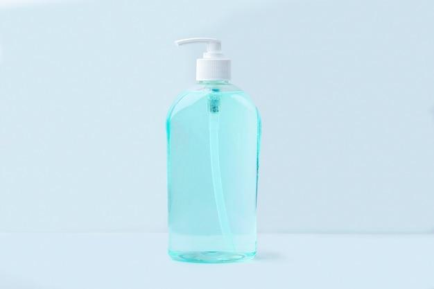 Große flasche mit antiseptischem desinfektionsgel zum händewaschen auf blauem hintergrund. alkoholgel als coronavirus-prävention. konzept zur vorbeugung von viruserkrankungen.