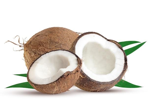 Große ganze kokosnuss und ihr teil mit grünen blättern