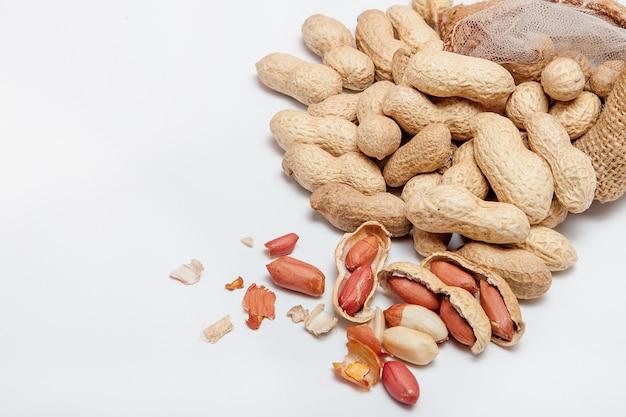 Große geschälte erdnüsse nahaufnahme von bohnen in der schale. ungeschälte erdnüsse in der schale. erdnüsse, für wand oder textur. wachsendes organisches protein.