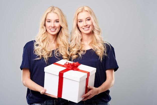 Große geschenkbox von blonden zwillingen getragen