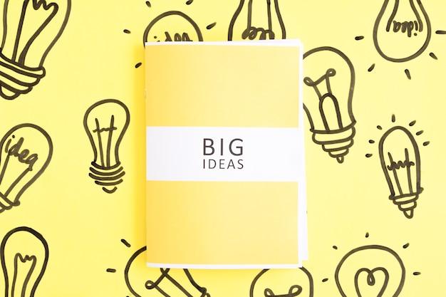 Große gezeichneter glühlampe des ideentagebuchs an hand auf gelbem hintergrund