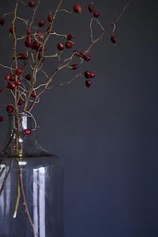Große glasflasche mit niederlassungen der trockenen roten hagebutte auf hölzerner tabelle, selektiver fokus