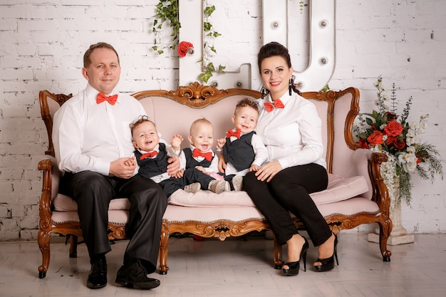 Große glückliche familie: mutter, vater, drillinge söhne