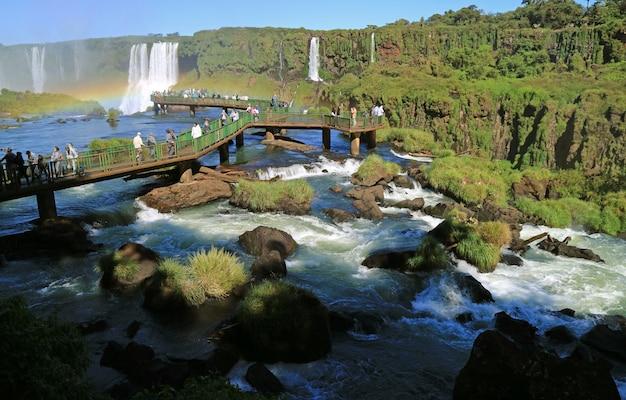 Große gruppe des besuchers auf der promenade unter dem starken strom, iguazu falls an der brasilianischen seite, brasilien