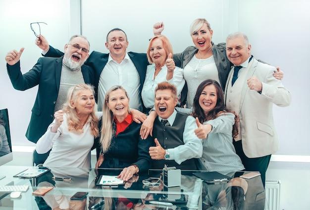 Große gruppe erfahrener mitarbeiter am arbeitsplatz im büro. das konzept der professionalität