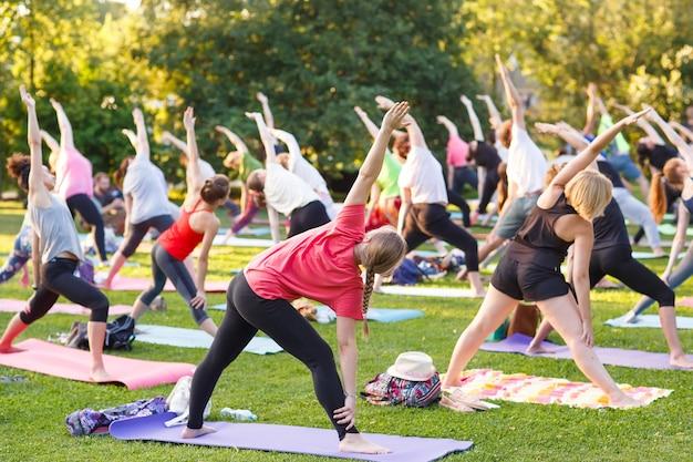 Große gruppe erwachsene, die an einer yogaklasse draußen im park teilnehmen