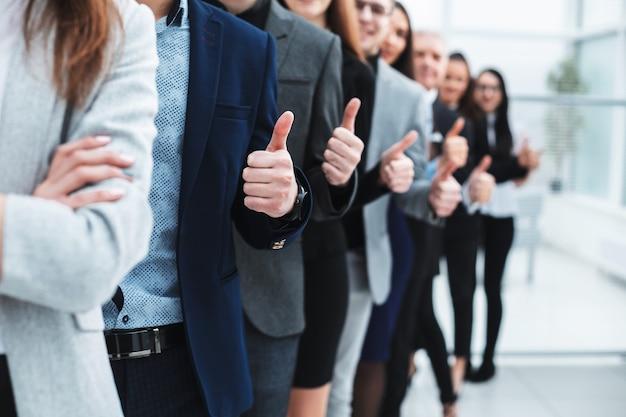 Große gruppe junger unternehmer zeigt daumen hoch