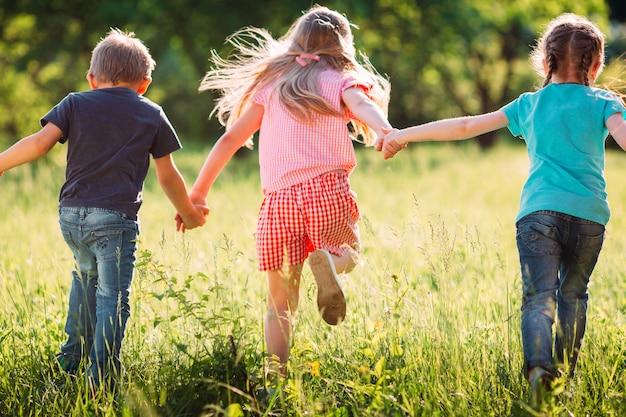 Große gruppe kinder, freunde jungen und mädchen, die in den park am sonnigen sommertag in der zufälligen kleidung laufen.