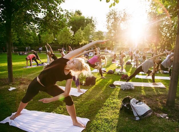 Große gruppe von erwachsenen, die einen yoga-kurs außerhalb im park besuchen