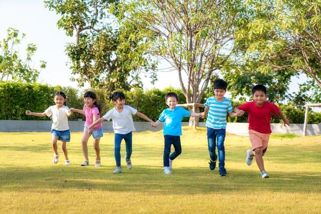 Große gruppe von glücklichen asiatischen lächelnden kindergartenkinderfreunden, die hände halten, die im park am sonnigen sommertag in freizeitkleidung spielen und laufen.