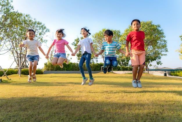 Große gruppe von glücklichen asiatischen lächelnden kindergartenkinderfreunden, die hände halten, die zusammen während eines sonnigen tages in freizeitkleidung am stadtpark spielen und springen.