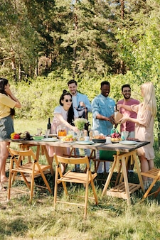Große gruppe von glücklichen jungen interkulturellen freunden, die taschen mit nahrungsmitteln vom supermarkt auspacken, während tisch für abendessen im freien dienen