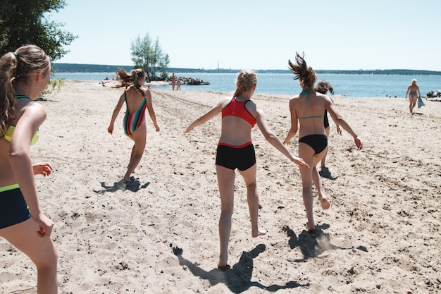 Große gruppe von kindern laufen an einem strand am meer entlang