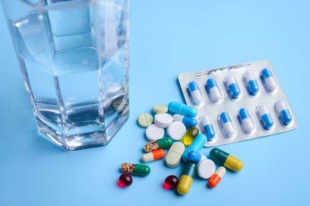 Große gruppe von pillen in der nähe von glas wasser