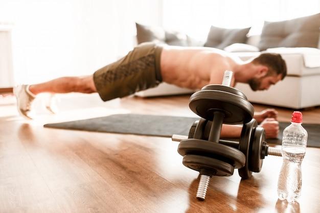 Große hanteln und wasser auf dem boden. junger mann, der zu hause sport treibt. schnittansicht des t-shirtless kerl-sportlers mit einer sportfigur in plankenposition.