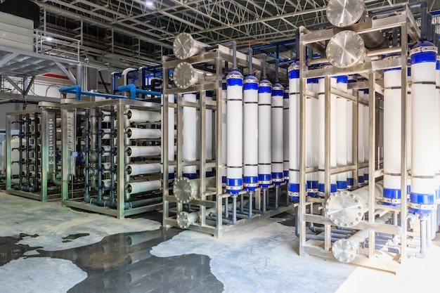 Große industrielle wasseraufbereitung und heizungsraum. glänzende stahlmetallrohre und blaue pumpen