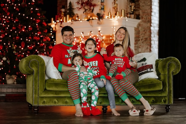 Große junge fünfköpfige familie im weihnachtspyjama, die zusammen auf einem sofa gegen weihnachtseinstellung sitzt.