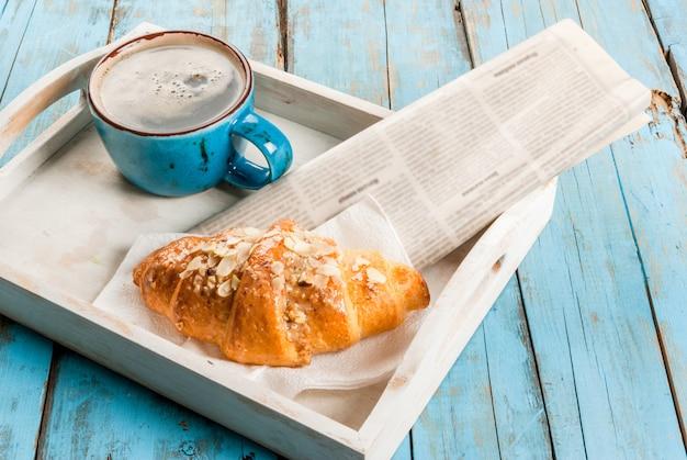 Große kaffeetasse, croissant und zeitung