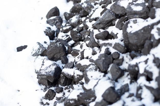 Große kohlenstücke unter dem schnee. brennstoff für den ofen im winter. ein haus auf dem land heizen.