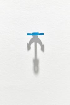Große lange schatten vom blauen plastikanker auf einem hellgrauen mit kopierraum. draufsicht.
