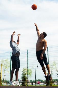 Große männer, die auf basketballplatz springen