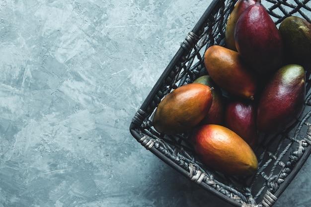 Große mangos in einem weidenkorb auf grauem hintergrund. gesundes essen, vegan