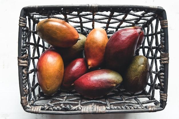 Große mangos in einem weidenkorb auf weiß