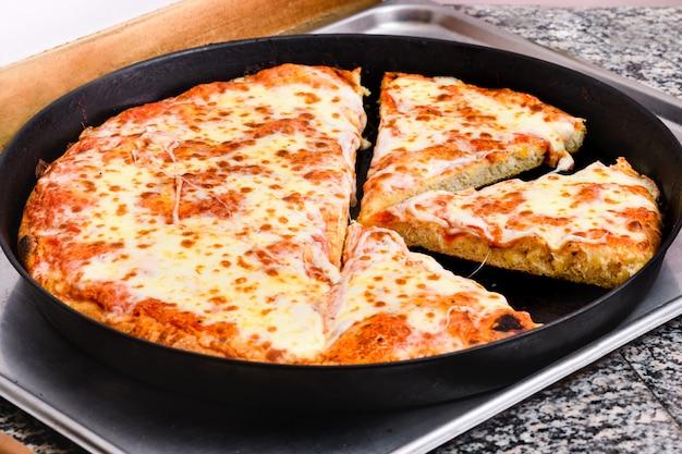 Große margherita-pizza in einem backblech geschnitten