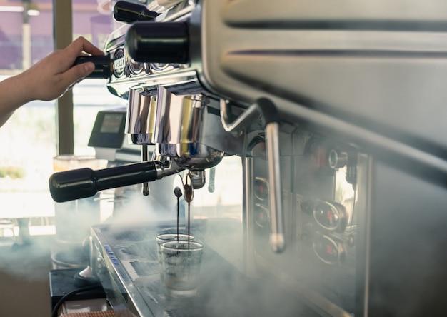 Große maschine der kaffeemaschine, die auf cup gießt