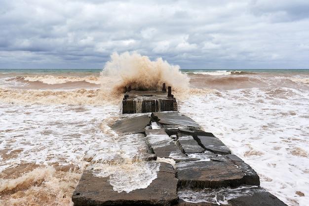 Große meereswelle mit spritzern stürzt auf einem wellenbrecher aus stein ab