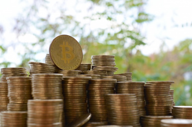 Große menge von bitcoin-stapeln auf unscharfem grünem baumhintergrund. kryptowährungs-handelskonzept