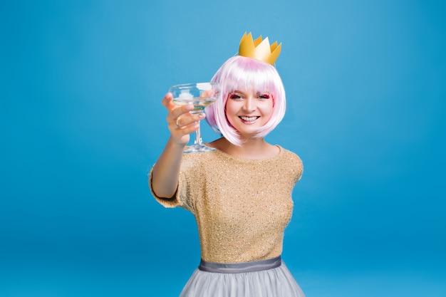 Große neujahrspartyfeier der freudigen jungen frau mit geschnittenem rosa haar in goldener krone. modisches modell, champagner trinkend, partyzeit, geburtstag, lächelnd.