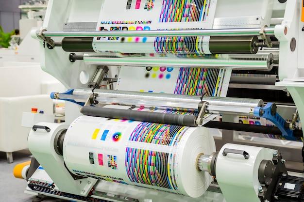 Große offsetdruckmaschine mit einer langen papierrolle in der produktionslinie einer industriedruckermaschine.