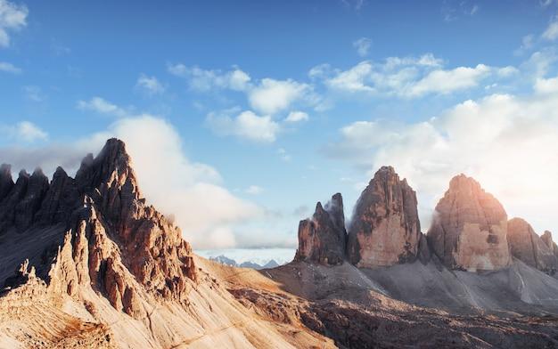 Große paternkofel und tre chime berge in einem bild mit nebel auf der spitze und bewölktem himmel.