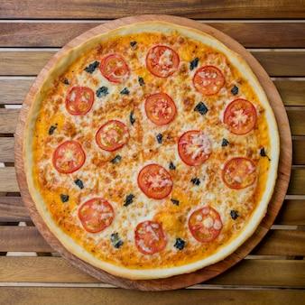 Große pizza auf einem holztisch. restaurant.