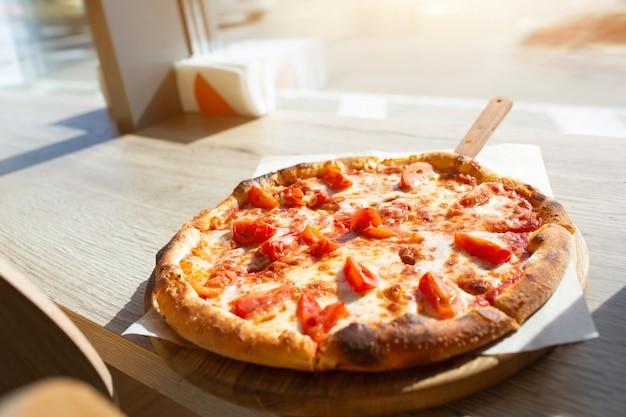 Große pizza steht auf einem tisch in einem café. italienische pizza in stücke geschnitten.