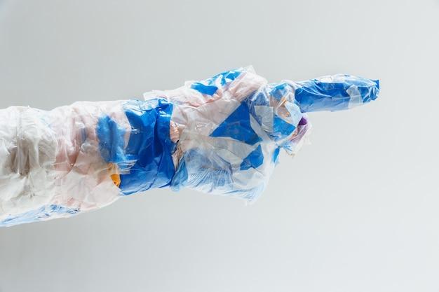 Große plastikhand aus müll auf weiß