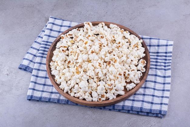 Große portion knuspriges popcorn auf einem holztablett auf einem handtuch auf marmorhintergrund. foto in hoher qualität