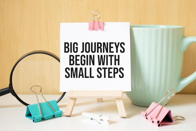 Große reisen beginnen mit kleinen schritten, die auf einem schwarzen notizbuch mit lupe und einem stift geschrieben sind. geschäfts- und leistungskonzept.