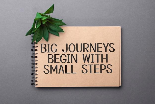 Große reisen beginnen mit kleinen schritten text auf handgefertigten farbigen notizblock und grüner pflanze
