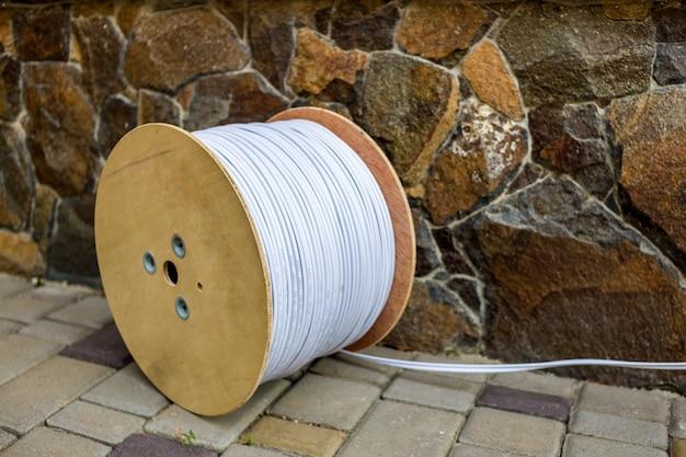 Große rolle des weißen industriellen elektrischen kabels auf großer hölzerner spule draußen