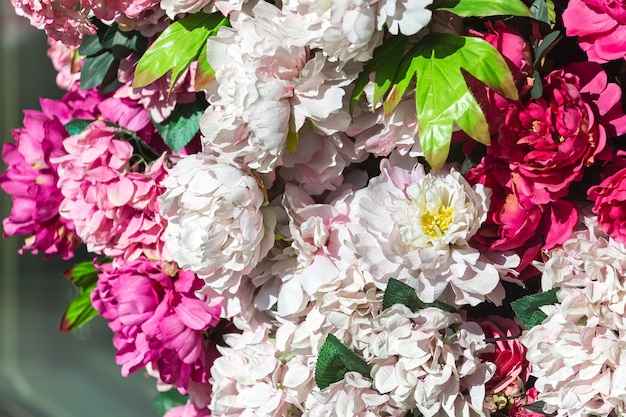 Große rosa und rote künstliche pfingstrosenblumen an der wand. zarte florale hintergrundtextur für hochzeitsszene, festliches dekor.