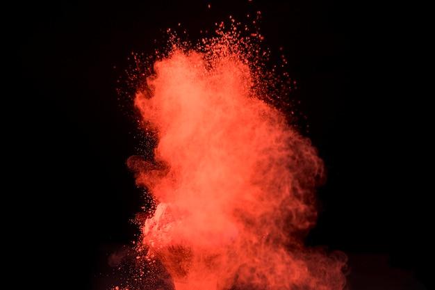 Große rote explosion des pulvers auf dunklem hintergrund