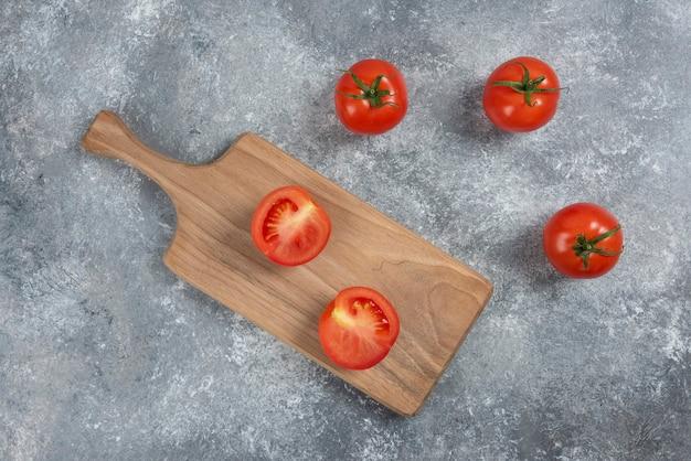 Große rote frische tomaten auf einem marmorhintergrund.