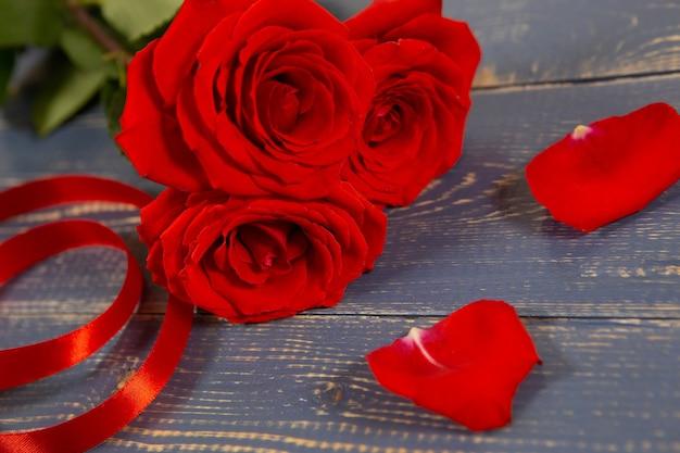 Große rote rosenknospen mit einem geschenkband und blütenblättern liegen auf einem hölzernen hintergrund.