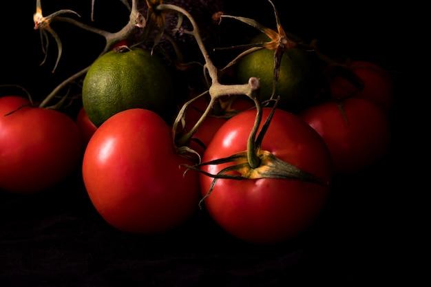 Große rote und reife tomaten in einem alten korb auf schwarzem