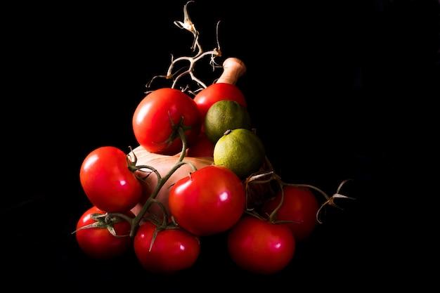 Große rote und reife tomaten mit einem mörser und einem stampfe im olivenholz auf schwarzem