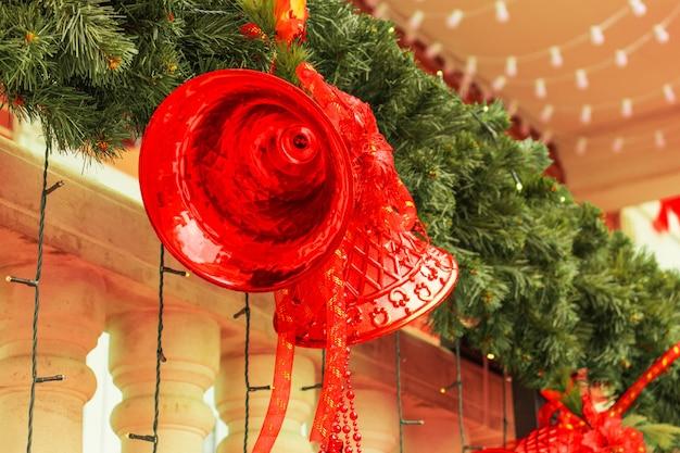 Große rote weihnachtsglocken mit schleifen, lichtern, grünen zweigen der weihnachtsbaumnahaufnahme. neues jahr 2021 und weihnachten, neujahrsstimmung, neujahrsdekorationen