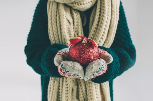 Große rote weihnachtskugel in den händen am mädchen. das kind trägt einen pullover, eine weihnachtsmütze und einen schal.