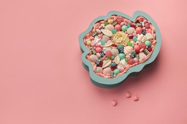 Große schachtel in form eines rosenknospens, gefüllt mit verschiedenen köstlichen süßigkeiten auf rosa